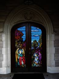 a door to a church is decorated with stained glass panels featuring angels make your