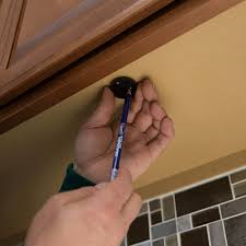 mounting cap in place beneath upper cabinet pencil marking pilot hole placement