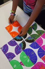Collaborative Art Activity - Circles with symmetrical designs are cut into