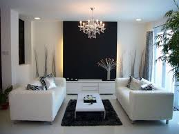 classic small chandelier with elegant white couches for modern art deco living room ideas with black accent wall