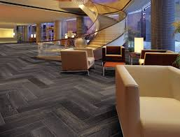 awesome dark grey faux wooden herringbone tile floor with beige vinyl tuxedo couch as well as curved glass stairs in luxury open floor loft plans