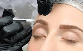 cosmetologist making permanent makeup attractive woman getting care and tattoo at