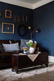 this living room smartly balances its dark blue walls and dark brown couch with white tulips and gold frames