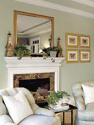 looks like a mirrored wall above the fireplace along with a round mirror leaning with 2 side fl arrangements