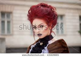 y woman with gothic makeup and red hair against old castle