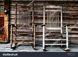 two old wooden rocking chairs on front porch part of door and the house s wooden
