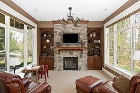this marvelous stone fireplace has a wooden mantle just under the television for extra storage space