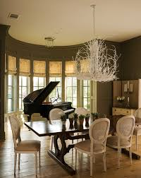 silhouetted against a demilune bay window a glossy black piano provides a dramatic focal point for a dining room painted earthy green the formal piano and