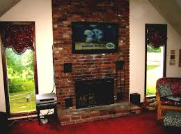 perfect mounted tv above a brick fireplace combined with book shelves and