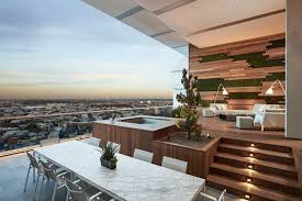this large modern furnished balcony features plenty of natural wood and includes an elevated seating area