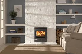 gray fireplace placed on the white wall plus floating white wooden shelves for ornaments placed on