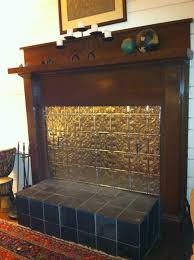 i made a fireplace cover out of cement backerboard and covered it with tin ceiling tiles