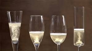 a of four diffely shaped glasses with sparkling wine and a mentos in each of