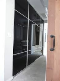 four sliding doors in a hallway three panels that are phantom black the middle