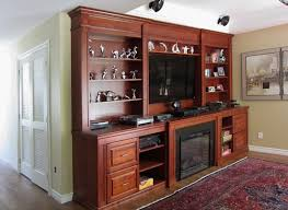 classic wall unit in cherry wood incorporating fireplace mantel tv surround and storage