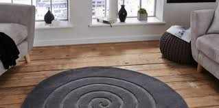 a circular living room rug under a grey sofa next to a shaded window