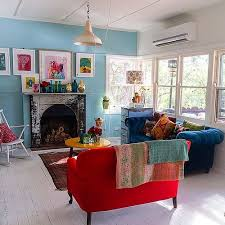 Red and blue sofa, turquoise walls, all that beautiful light and a yellow  table! In artist Paula Mills home. like this for living room