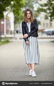 young beautiful girl in stylish streetwear black leather jacket long striped dress white sneakers and with