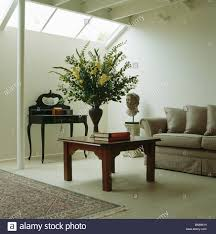 Living Room Extension Large Flower Arrangement On Wooden Coffee Table And Beige Sofa In