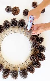 now take some tiny little pine cones and complete the inside circle our lovely diy pinecone wreath is ready for some creative final touches