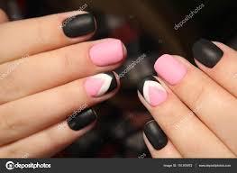 マットの黒とピンクの爪のマニキュアのデザイン ストック写真
