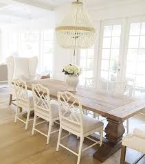 dining room decor ideas warm white color palette with wood table and beaded chandelier