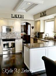 a medium contrast white or cream kitchen palette with quartz and dark wood flooring