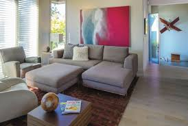 the monochromatic colour scheme in the remodelled living room offers a subtle background palette to let the art and rug pop