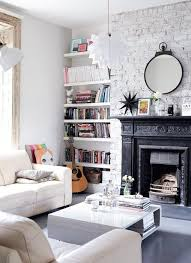 a bright white living room with modern furniture a white painted brick wall and a