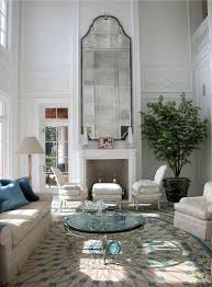 mirror and fireplace in high ceilinged living room in palm beach by bruce bierman