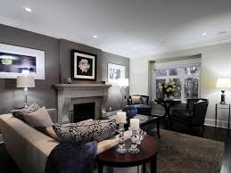 This living room features a dark gray accent wall situated behind a light  gray painted fireplace