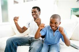 black family watching tv. young african boy watching television with his father - excited stock photo premium royalty- black family tv t