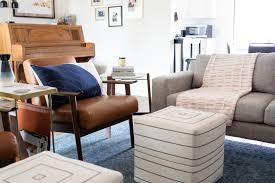 mid century modern living room with grey sofa leather chairs blue rug