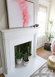 white painting tile around fireplace with white fireplace mantel light brown laminate hardwood flooring with white walls and ceilings light grey and brown