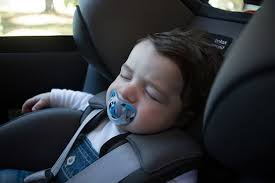 close up of young child with dummy sleeping in a forward facing car seat