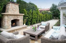 lovely patio features a taupe wicker sofa and chairs lined with powder blue pillows as well as a taupe teak coffee table facing a stone fireplace and hearth