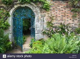 ornate wroughtiron gate set within a cotswold stone arch and 17th century brick wall rousham house oxfordshire england ornate wrought iron e51 gate