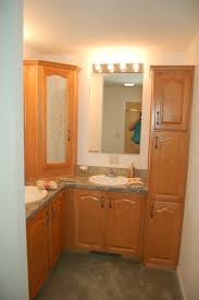 l shaped brown wooden vanity with marble top and double white sink