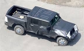this is a spy photo of a masked jeep wrangler pickup truck shot in july 2018