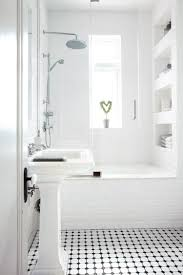 Small classic white bathroom with a shower-bath, wall unit and floor tiled  in black and white