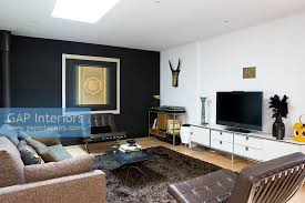 Contemporary living room with leather armchairs and black feature wall
