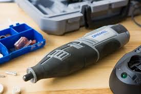 wood carving power tools. the cordless dremel 8220 sitting on a wooden board with its carrying case and drill head wood carving power tools