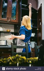 Woman Housewife In The Kitchen Girl Pulls Out From The Shelf