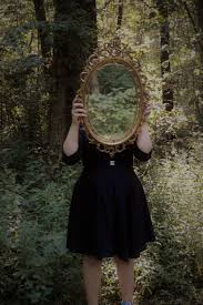 Woman Holding Mirror Against Her Head in the Middle of Forest Free