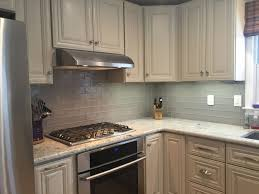 grey glass subway tile kitchen backsplash with white cabinets