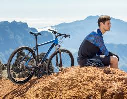 cyclist in muddyfox short sleeve jersey and shorts sat next to his bike on a mountain