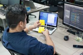 developer office. asian business man yellow sticky note rear back view thinking idea computer developer working desk laptop sitting real office stock photo colourbox