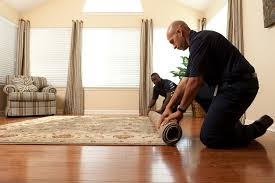 two technicians roll an area rug