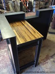 Stand Up reception desk made by Carbon Industrial using blackened steel and  reclaimed bowling alley wood