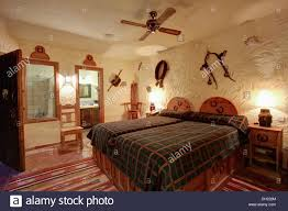Spanish Bedroom Furniture Electric Ceiling Fan Above Wooden Bed With Brown Checked Cover In